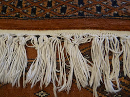 Before repair at the fringes on an oriental carpet