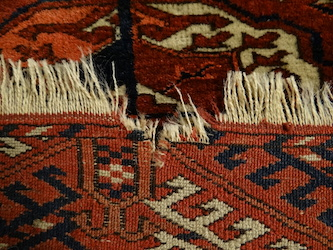 Before restoration of the fringes of a Turkoman carpet